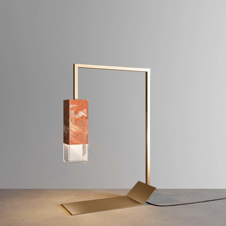 Featuring a bright frame in satin brass, this limited-edition table lamp is marked by a sculpted profile, the sidearm supporting the shade that stems from the lifted side of the plate functioning as the base of the whole. This harmonious piece