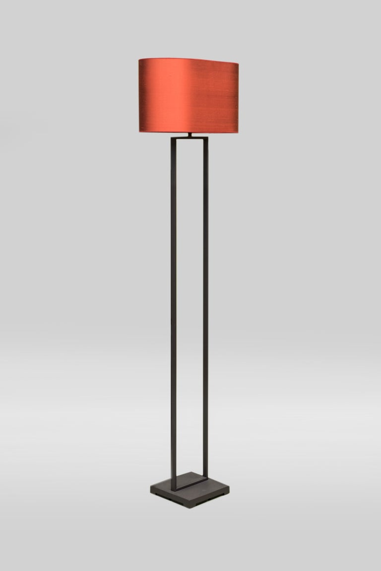 This minimalistic lamp 'Tom' by GHYCZY has a rectangle shaped stainless steel brushed frame. The 21th Century floor lamp has a light red oval shaped lampshade. The square pedestal is made of sand casted aluminium. Besides being a designer, GHYCZY's