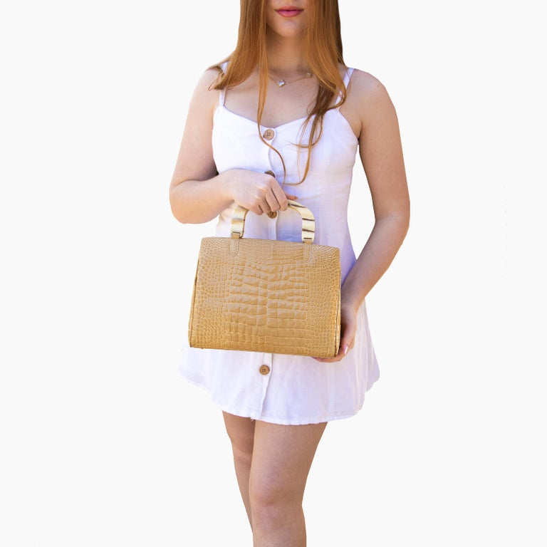 Stunning genuine crocodile handbag. This bag has a double zippered middle section with crocodile appointments. Within this, there are 3 side pockets and a 4th zippered pocket. This bag also has a pocket either side of the zippered middle section,