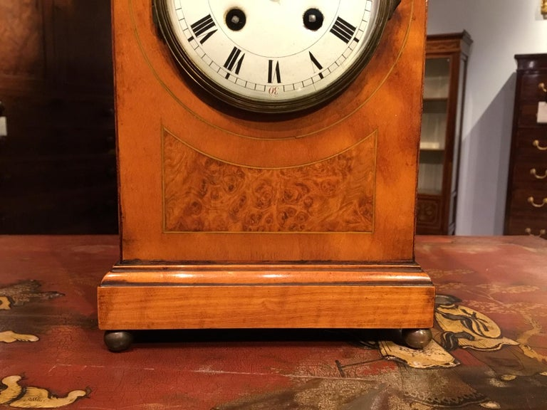 A satinwood Edwardian period lancet shaped mantle clock. The lancet shaped case in satinwood with an amboyna inlaid panel. Having a circular enamelled dial and a brass movement striking a gong on the half hour and hour. Raised on four brass ball