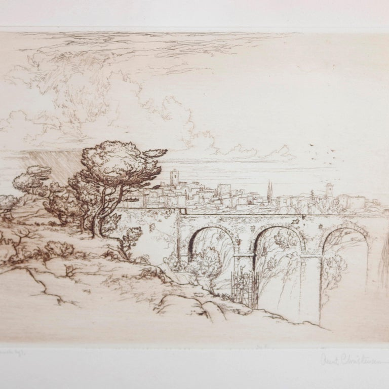 A landscape etching by Arent Christensen depicts figures working on stone bridge in river gorge setting, artist-signed as photographed, seated in tiger maple frame, 20th century  Measures: 16.5