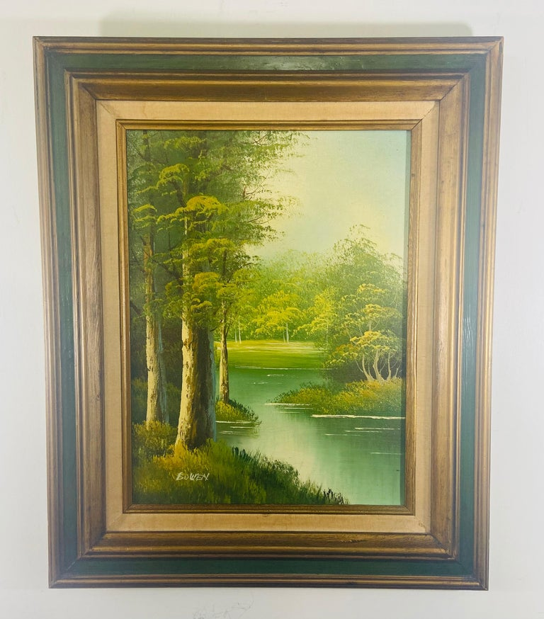 An oil on canvas landscape painting featuring a peaceful scene of a river in the middle of the wood. The painting is made in green color tone. The art work is finely framed in custom handmade wooden frame painted in dark green and gilt color. This