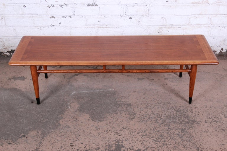 A gorgeous Mid-Century Modern coffee table from the Acclaim line by Lane. The table features beautiful walnut wood grain and unique dovetail joint design. It sits on tapered legs with a sleek stretcher connecting the legs and adding to the design.