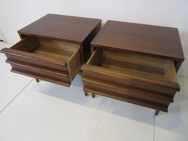 A pair of walnut Minimalist nightstands / end tables with drawers sitting on simple slender legs for a light feel, manufactured by the Lane Altavista Furniture company from their Rhythm collection. These nightstands can be matched with any type of