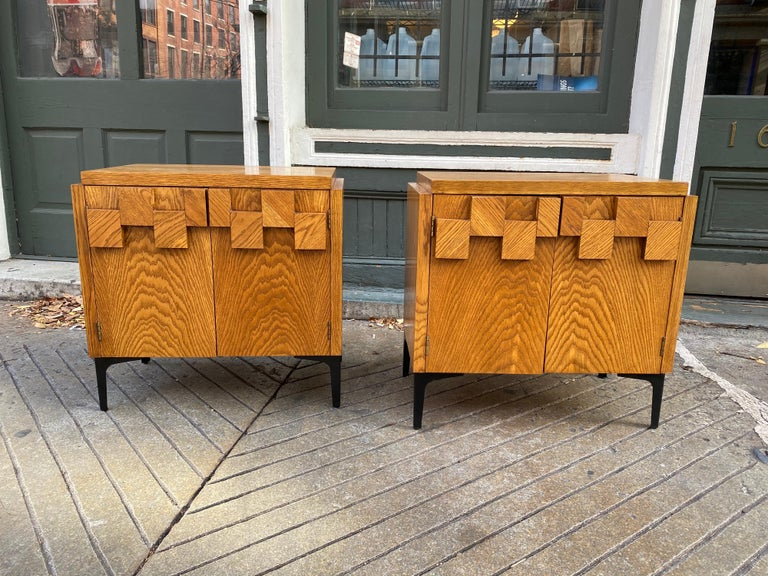 Nice matched pair of Lane end tables or nightstands in their original finish. Cubist feel to the top of each door. Rich grain throughout. Black iron legs give a nice juxtaposition to the wood cabinets.