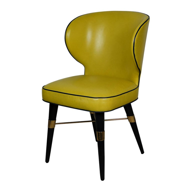Upholstered in velvet or leather, a Classic design radiates from this chair's modern lines. The Langston dining chair features solid walnut legs with brass accents. COM available.