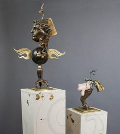 """The Lovers"", gold and bronze colored figures, stand on paired pedestals"