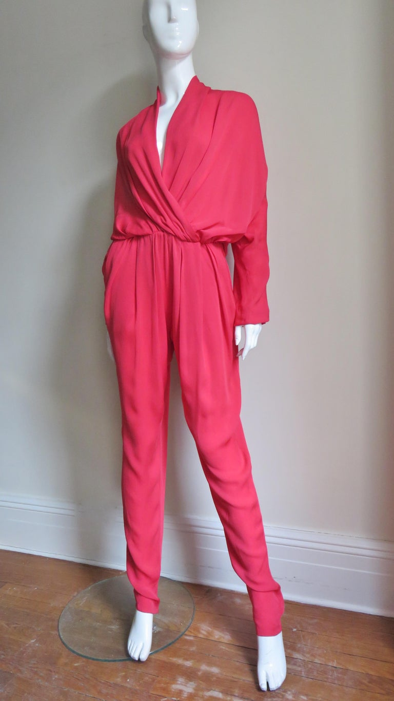 A fabulous red jumpsuit from Lanvin S/S 2014 collection.  It has a draped overlapping front creating a plunging V neckline, full dolman with stretch at the wrists and waist.  The pant legs are full tapering down to zippers at the ankles and there