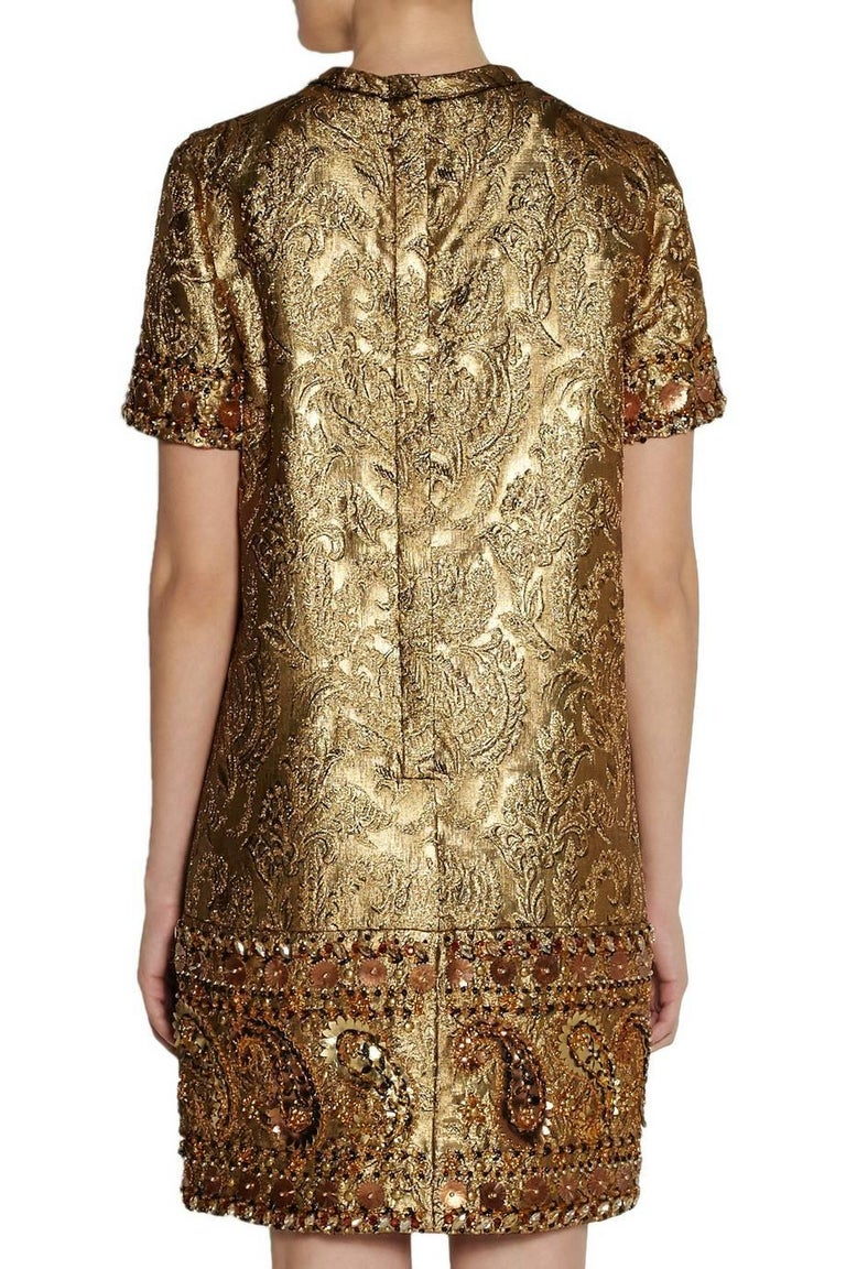 Lanvin cocktail shift dress comes in metallic gold jacquard fabric and features a raw edge crewneck, short sleeves, frontal pockets, and heavily embellished trim with embroidery, beading, rhinestones, and copper and gold metallic leather appliques.
