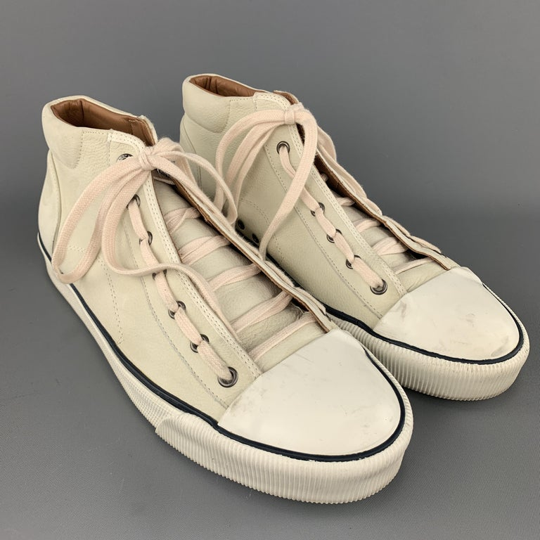 Lanvin sneakers come in creamy beige textured leather with a white rubber toe cap and pink laces. Made in Spain.    Very Good Pre-Owned Condition. Marked: UK 10  Outsole: 12 x 4 in.