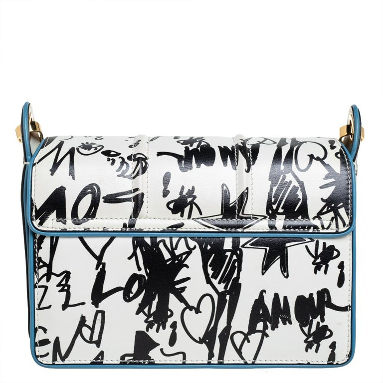 This stylish Jiji shoulder bag from Lanvin is crafted from leather. The bag features a black-white graffiti-like print all over, a shoulder strap, and a gold-tone lock on the front flap. The flap opens to a fabric-lined interior that houses a zip