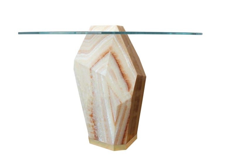 A solid block of peach onyx, quarried in Mexico, sculpted and hand finished serves as a dramatic base for this dining table. The Lapidary dining table can be carved from an infinite variety of colorful stones, offering limitless options of color and