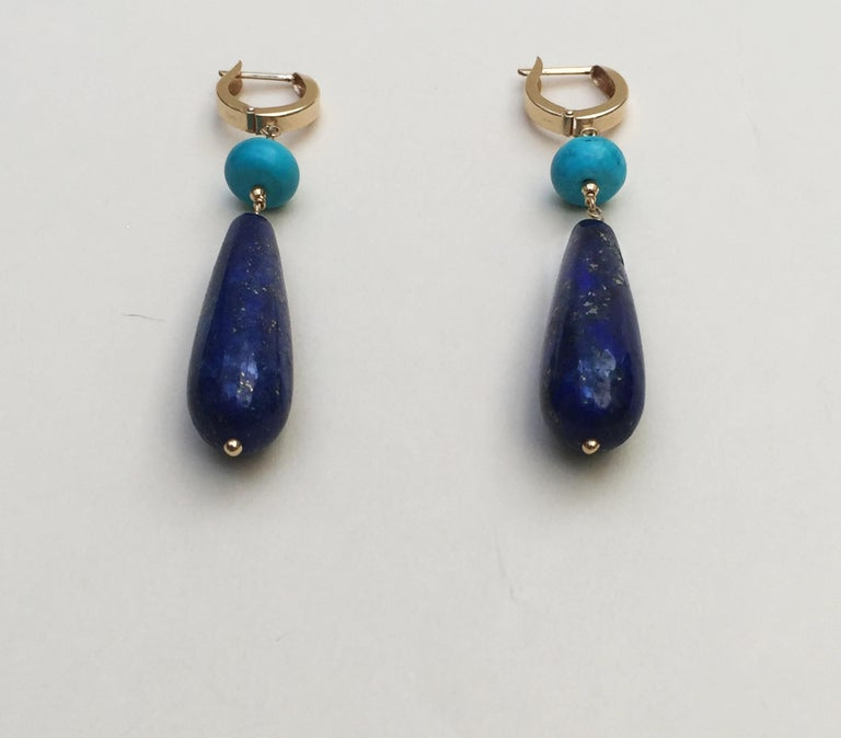 These lapis lazuli and turquoise earrings are highlighted with 14k yellow gold faceted beads and lever backs. Shimmering within the lapis lazuli are veins of gold, adding a natural shine to the earrings. Accenting the deep blue of the lapis lazuli