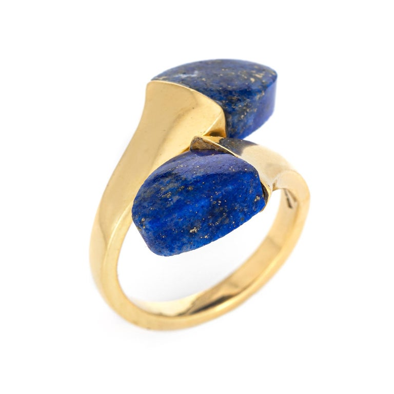 Stylish vintage lapis lazuli bypass ring (circa 1970s to 1980s) crafted in 18 karat yellow gold.   Two pieces of lapis lazuli measure 10mm x 9.5mm. The lapis is in excellent condition and free of cracks or chips.   The lapis lazuli is set in a