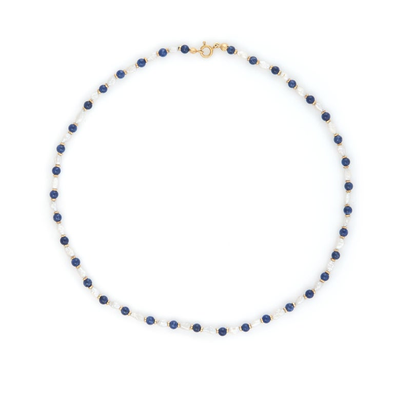 Finely detailed choker necklace, strung with freshwater pearls and lapis lazuli. 14k gold bead separators add texture and contrast to the necklace.   16 inch length and in excellent condition.  Particulars:  Weight: 8.9 grams  Stones: Freshwater