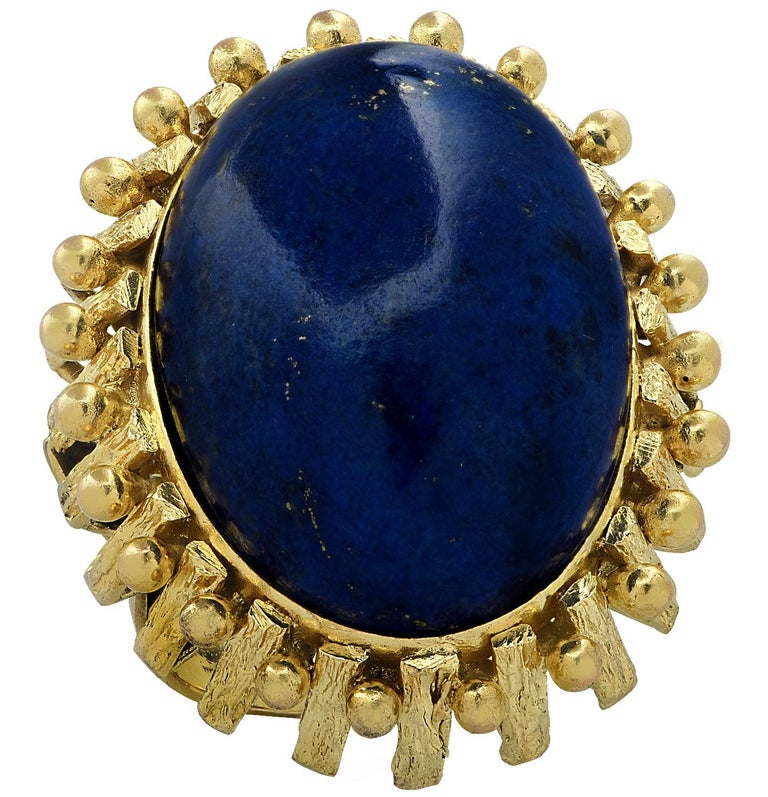 Striking cocktail ring crafted in yellow gold, showcasing an impressive oval Lapis Lazuli cabochon measuring 25mm x 17.8mm. The face of this majestic ring measures 1.2 inches in length and 1 inch in width. The shank measures 4.27 mm tapering gently