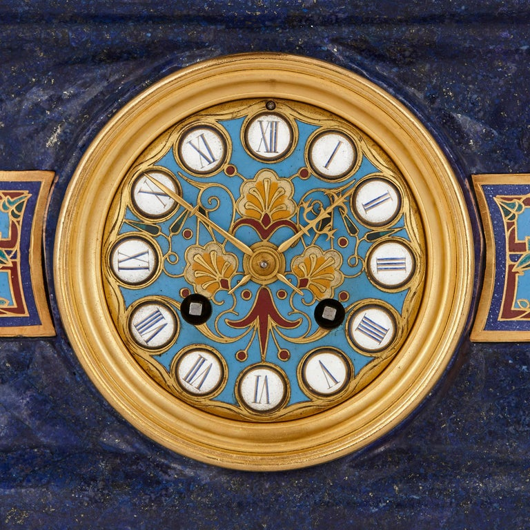 Inspired by the art and culture of Classical Greece, this three-piece garniture contains a mantel clock and two candelabra. The rectangular body of the clock is of lapis lazuli and is surmounted by a Grecian vase, also of lapis. The body of the