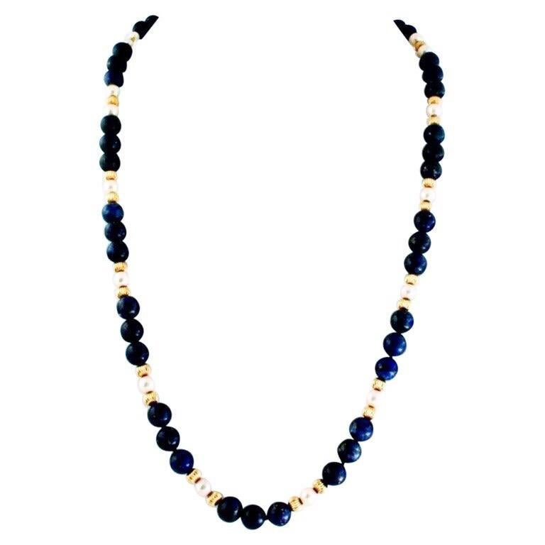 The lapis, pearl, and gold vermeil necklace with matching long dangle gold vermeil earrings is my own creation. The necklace is an earlier and more formal design. I made the earrings afterwards to accent the necklace's gold tone beads. The long