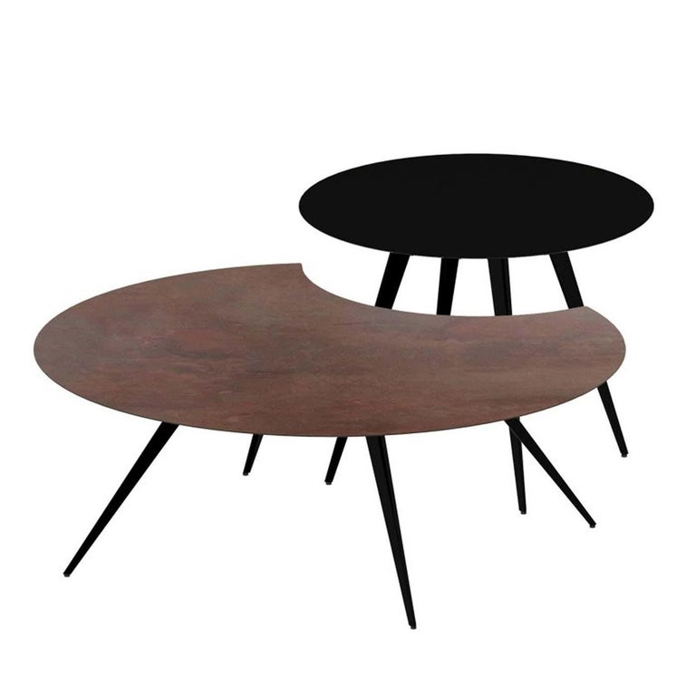 Defined by a captivating high-low geometry of great visual impact, this set of two side tables can be set separately or together to create a unique look. The frames are made of laser-cut steel sheets in epoxy-painted copper black with a sand texture