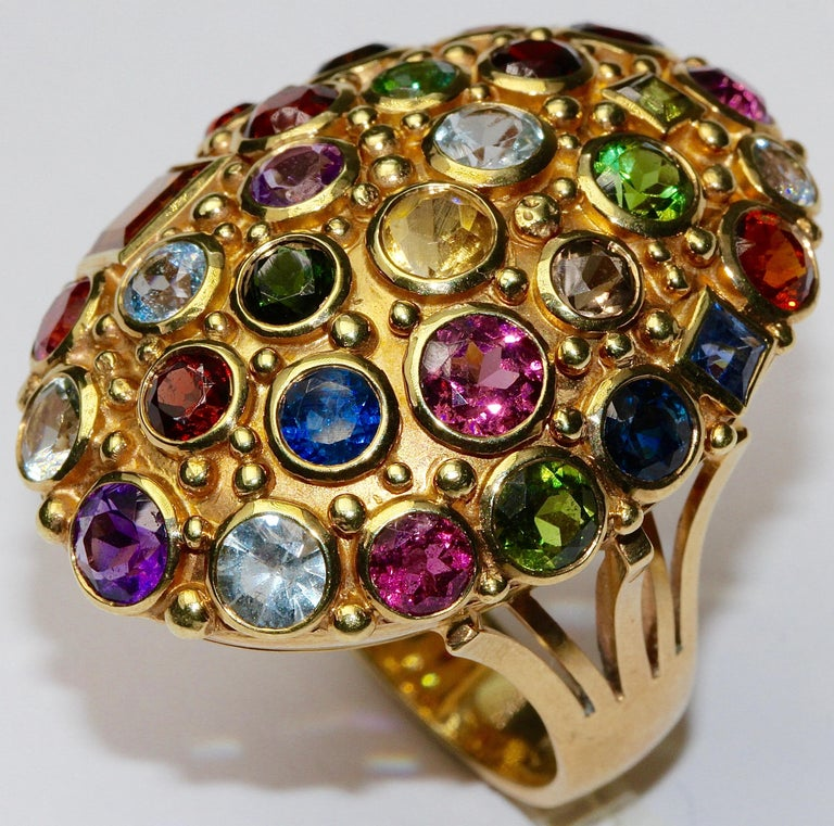 Beautiful and very fancy ladies cocktail ring. 14ct gold, hallmarked. The ring is studded with several gemstones, e.g. with aquamarine, tourmaline, amethyst, smoky topaz, citrine, ruby, sapphire, blue topaz.  Finest goldsmith work.