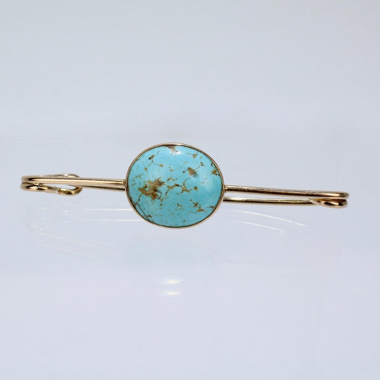A very fine 14k gold and turquoise scarf pin or brooch.  Fashioned as a bar pin and bezel set with a beautiful turquoise matrix cabochon to the center.  The reverse having a coiled spring and straight pin that is secured in a safety-pin