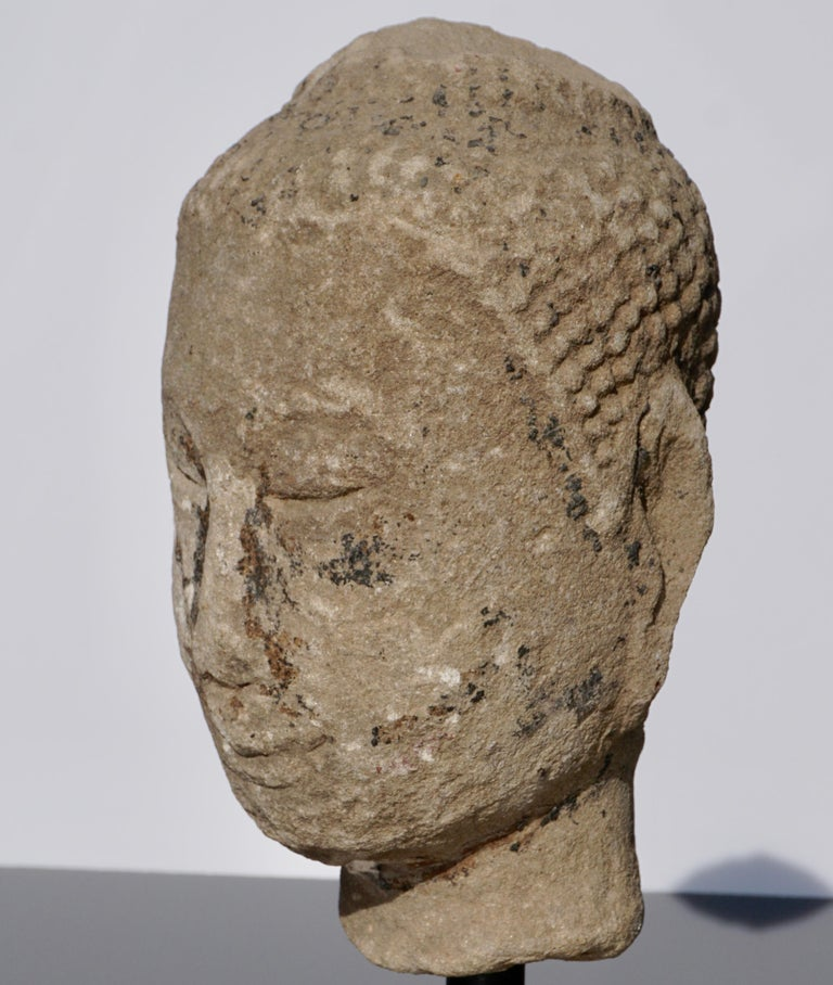 A very serene and calming weathered sandstone Buddha head from Thailand, circa 16th century or earlier. Traces of polychrome and golf pigments throughout. Gilding around nose looks like tears eminatinting from Buddha's tear ducts.. I love the