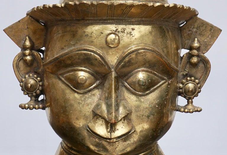 A Indian Mukhalingam Mukha face Lingum mask.  large and decorative gilt bronze Shiva facial representation of a Hindu God for phalic Lingums. A rare ritual artistic artifact.  Dimensions: 18.25 x 12.5 x 5.5 inches (46.4 x 31.8 x 14.0 cm)  Condition: