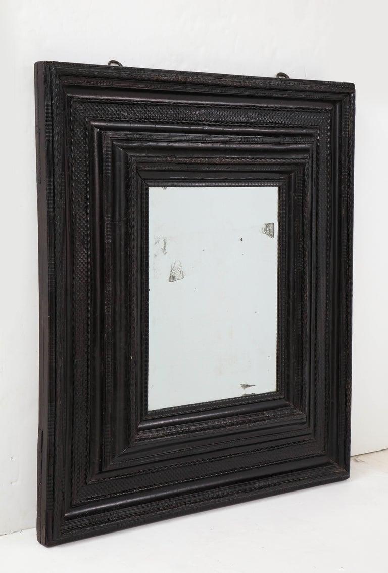 Large 17th C Italian ebonized walnut guilloche mirror with original glass Walnut, mirrored glass Measures: H 47.5, W 41.5 in.