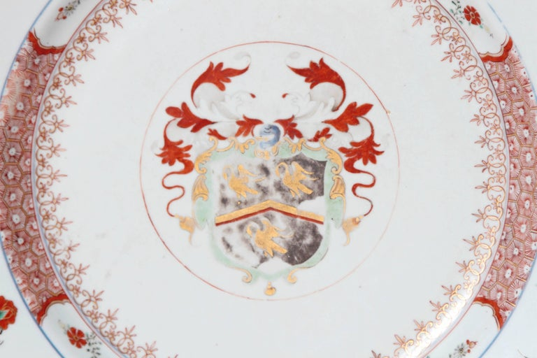 An impressive 18th century Chinese export armorial charger. Crest in center of plate with floral sprays around the border. Decorative bands around of plate and the rim. White background with orange and gold, 18th century, China.