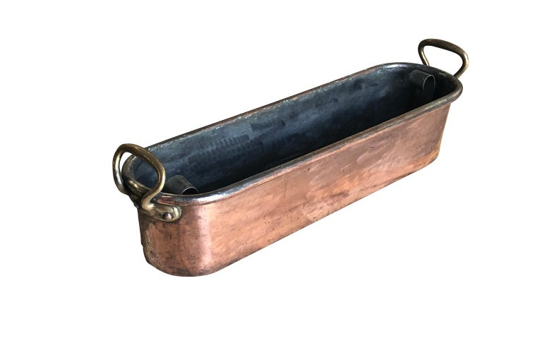 A large 18th century fish pan in copper from the South of France. The pan retains its original poaching tray. Five wholes have been punched into the bottom of the pan.  Wonderful quality. A great addition to a copperware collection.