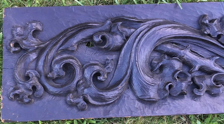 Large Colonial Pennsylvania carved frieze, an 18th century hand-carved pine single board panel with deep bas relief acanthus leaf scrolls against a scoop carved background. Panel is in its original dark matte finish, and retains a paper label on the