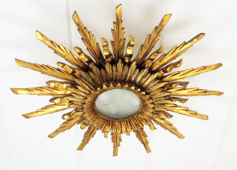 An spectacular gold leaf gilt sunburst flush mount or ceiling light fixture in Baroque style made in Spain, circa 1930-1940. Large size with two layers of beams in different sizes that make this piece gorgeous and highly decorative even more face to