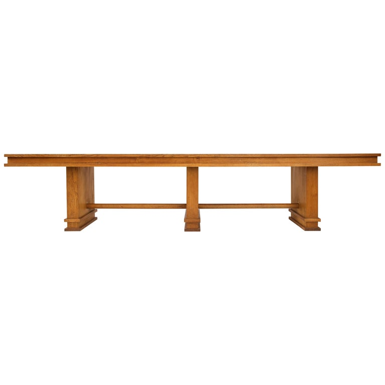 This monumental piece is broad and muscular. Defined by simple stately geometry. It will serve well as a large console, entry table, library table or shallow dining table.   It is possible to replace the green laminate panels with leather,