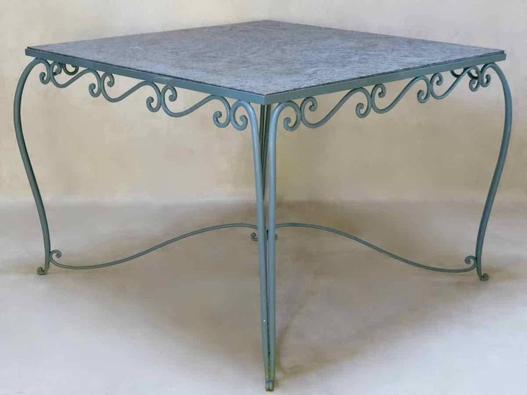 Elegant Art Deco square outdoor dining table. The wrought iron base is painted a delicate grey color. It has a scrolled apron, cabriole legs, and is joined by an pretty X-shaped stretcher. Dappled grey granite top.