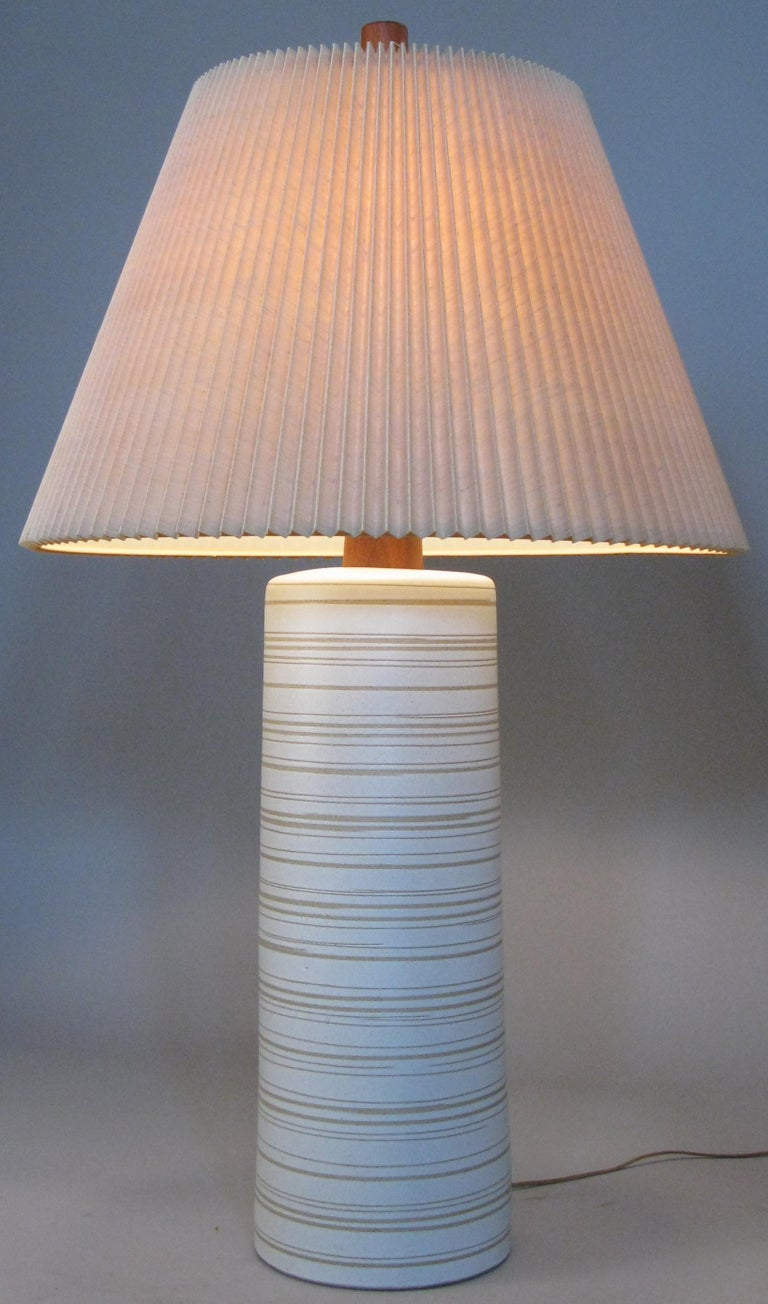 A very large vintage 1960s glazed ceramic table lamp by Gordon Martz for Marshall Studios, with a walnut neck and the original walnut finial. The lamp is off white with grey and taupe colored details. The linen pleated shade may also be original to