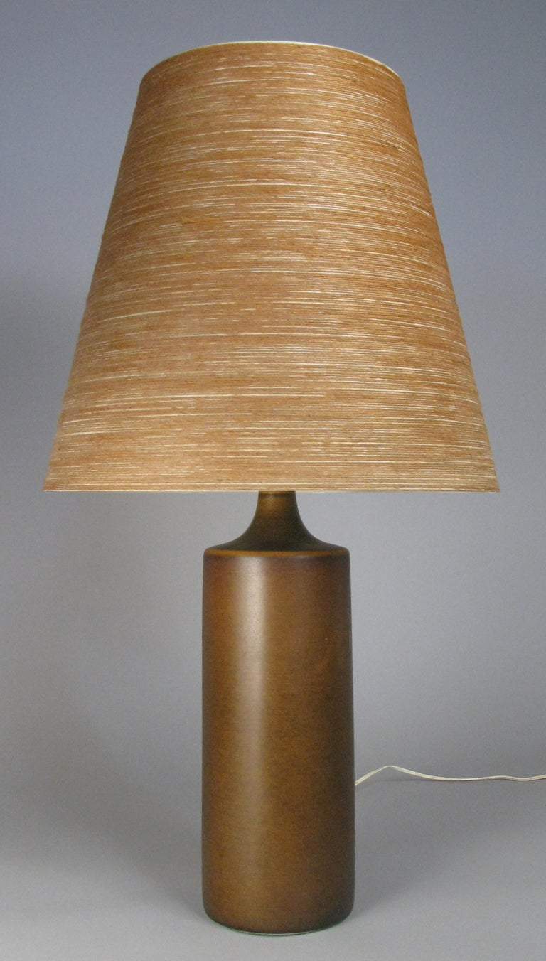 A very handsome 1960s Danish ceramic lamp by Lotte & Gunnar Bostlund, with a cylinder shape, in a medium brown color with the original jute wrapped shade.
