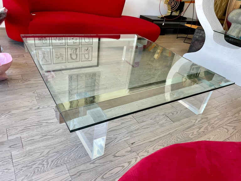 Very stylish large 1980s lucite coffee table in very good condition. The base of this coffee table is composed by four thick lucite pedestals and two stainless steel bars resting on top. The glass top is 3/4 of an inch thick with few hairlines