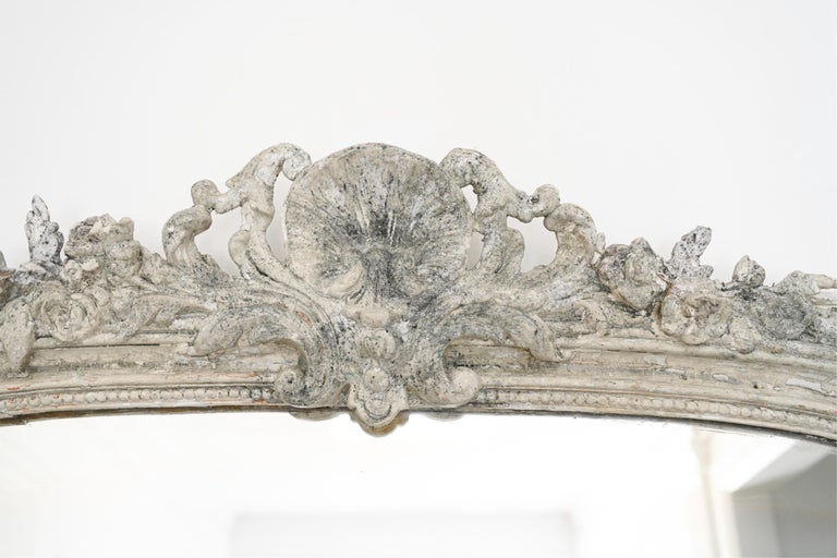 A rare impressive large scale antique Italian mirror, originally gilt, now with many layers of paint and faux antiquing. Mirror has beautiful carved details Perfect as a floor or full length mirror with height and width. Back with new support for