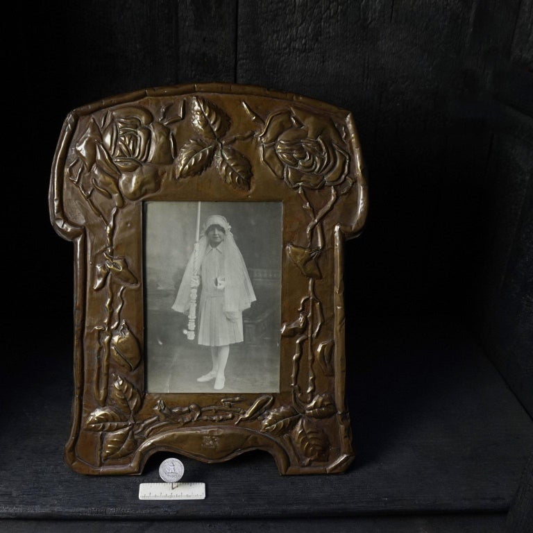 This lovely large latten picture frame with floral decoration was very modern for its time. It was inspired by the Arts & Crafts tradition and therefore made without machines or moulds. True craftsmanship, made from a brass plate hammered and