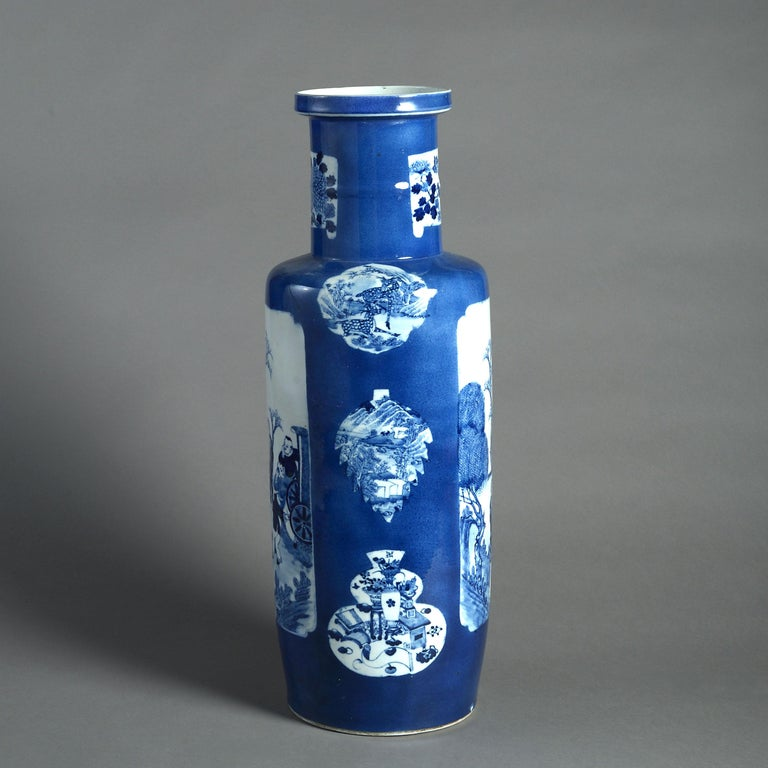 A large-scale blue and white porcelain rouleau vase, of good scale and decorated with cartouches on a powder blue ground.   Qing dynasty. With invisible restoration.