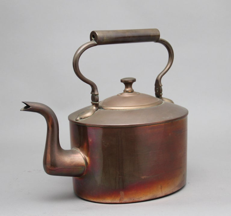Large 19th century brass copper kettle, having a shaped handle, acorn finial on the lid and a shaped spout, circa 1860.