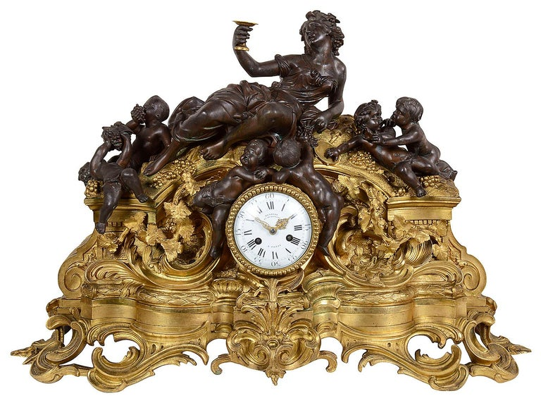 A very impressive 19th century Louis XVI style Bachuss influenced bronze and gilded ormolu clock garniture. The pair of four branch candelabra each supported by bronze putti, raised on gilded ormolu tripod bases with shell and rams head mount. The