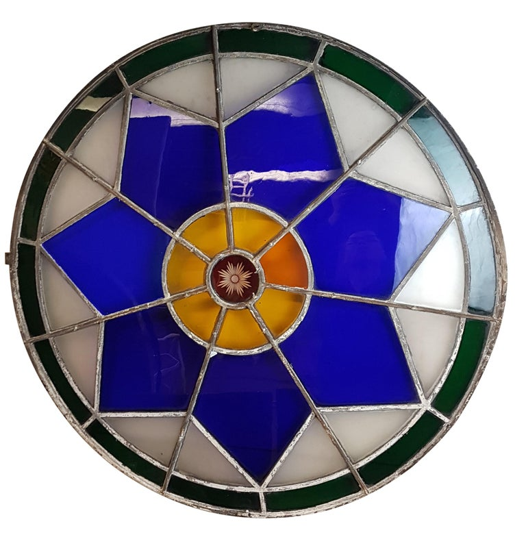 A truly stunning large original 19th century leaded stained glass circular window with cast iron frame. Majority of the glass is original with great rippling, has an etched ruby glass centre surrounded by amber glass (one of which is replaced), this