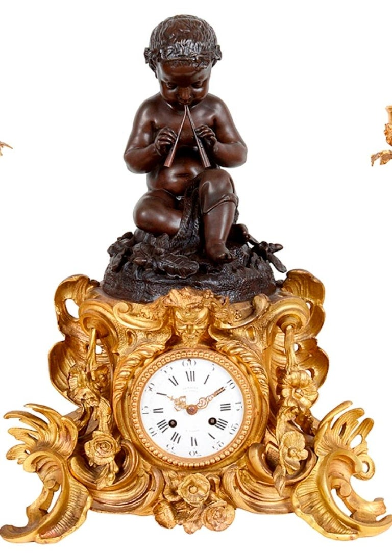 An enchanting 19th century French gilded ormolu and patinated bronze Louis XVI style clock garniture. The four branch, Rococo influenced candelabra each supported by three classical putti.  The clock with a bronze seated boy playing the pipes,
