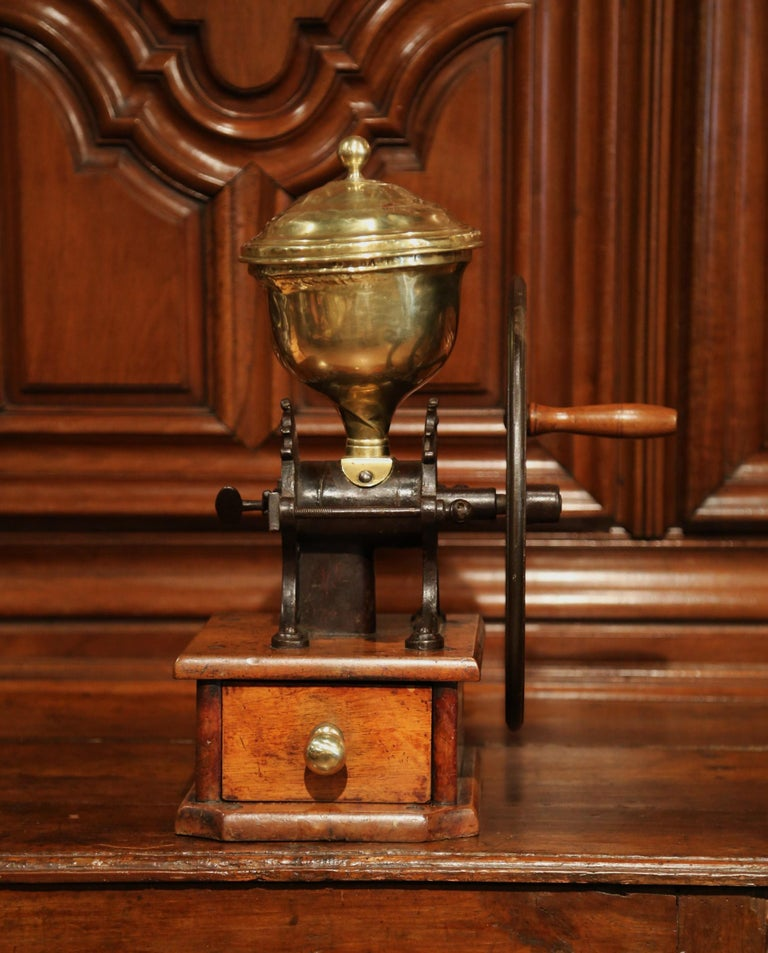 Make your own fresh, morning coffee with this unique, antique coffee grinder. Created in France circa 1850, the decorative coffee grinder features a large brass coffee compartment at the top, a cast iron wheel with a wooden handle on the side, and a