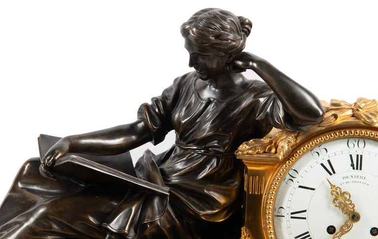 A large and impressive 19th century gilded ormolu and bronze Louis XVI style clock garniture, having a reclined classical lady reading, next to a white enamel clock face with an eight day chiming clock, signed Deniere, Paris. Raised on a base with
