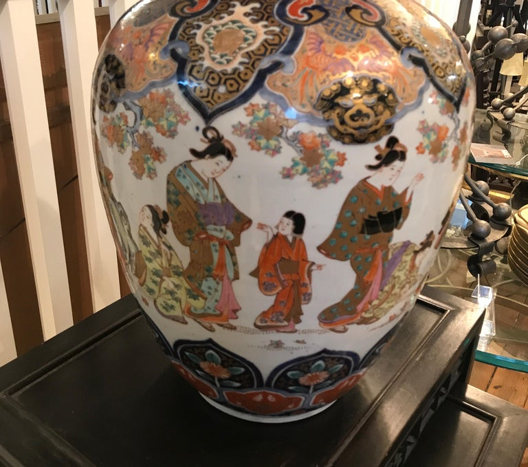 A remarkable hand painted Japanese porcelain Imari vase. Classic iron red and cobalt blue on a white porcelain background. Elegant Japanese figures painted all around the center portion with intricate detailed top and bottom with gilt highlights.