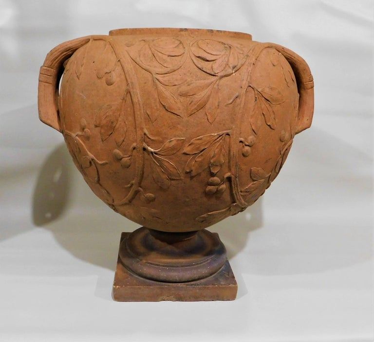 Italian terracotta urn/vase decorated with a grape vine design. Urn comes off the base.