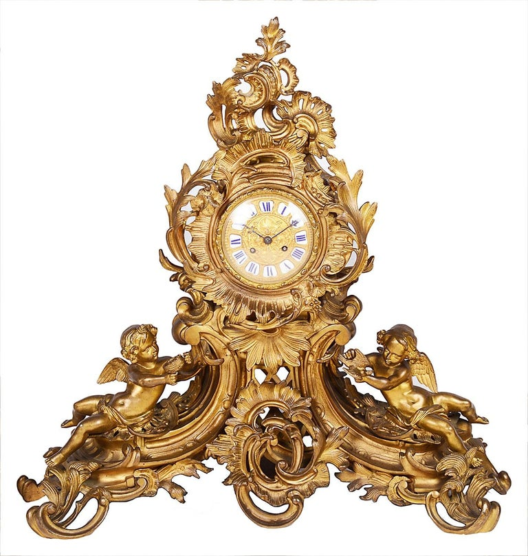 A large and impressive, 19th century gilded ormolu Louis XVI style clock garniture. Having scrolling foliate decoration with cherubs supporting the eight branch candelabra and either side of the clock. The clock having an eight day duration,