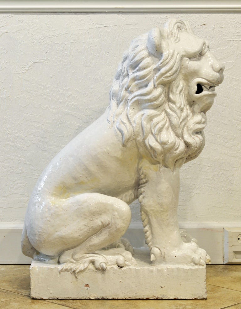 Sitting on a low square base and standing 35 inches tall this Italian white glaze terracotta lion is well modeled with dramatic detail and the rustic glaze adds character to the form.